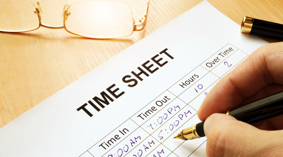 person completing a paper timesheet